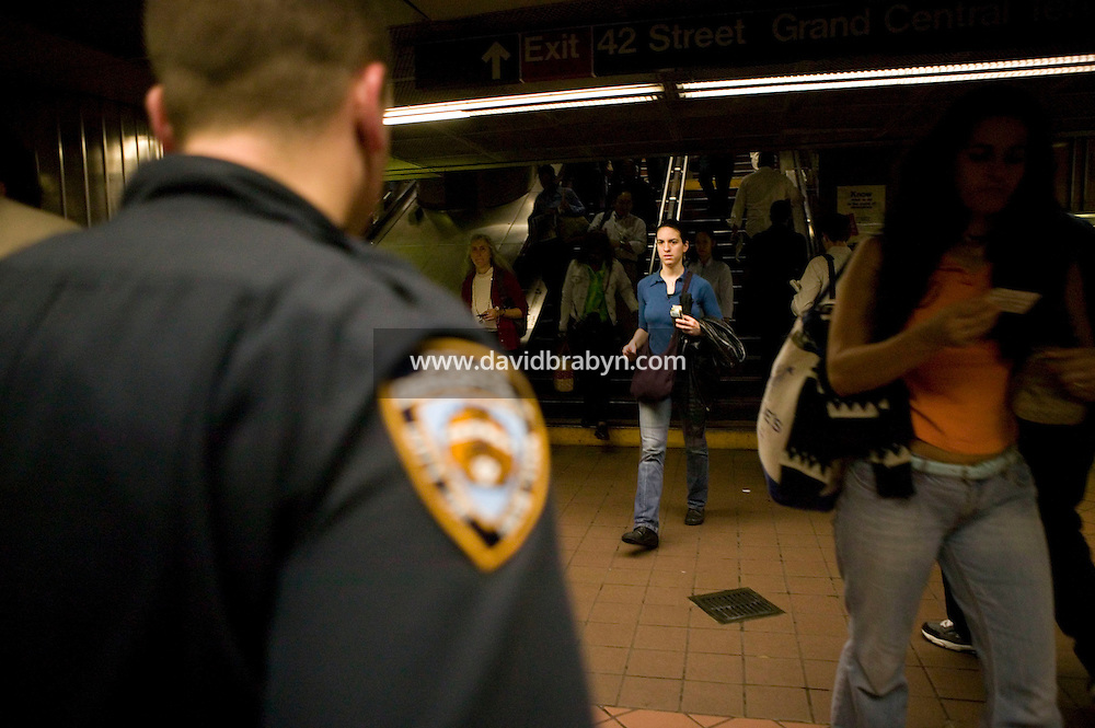 7 October 2005 - New York City, NY - A New York City police officer (L) stands guard as people arrive at the entrance to the Grand Central-42nd St subway station in New York City, on 7 October 2005, the day after the Police Department announced a specific terrorist threat to the subway system had been identified. Photo Credit: David Brabyn.