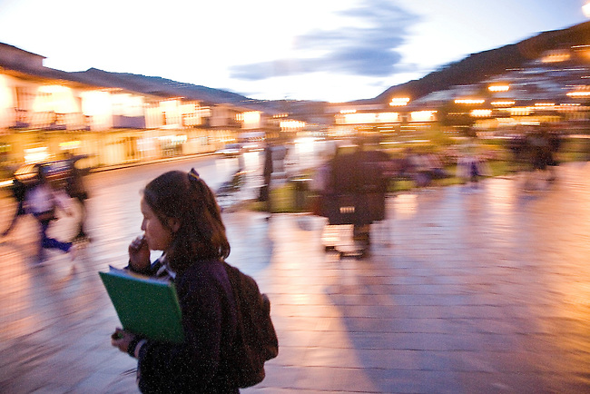 YOUNG PERUVIAN SCHOOLGIRL STRIDES HOME AMONGST THE CHAOS IN THE STREETS OF CUZCO