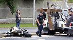 WATERBURY CT. 15 August 2017-081517SV06-A police officer checks on a motorcycle that was involved in a crash on Hamilton Avenue in Waterbury Tuesday.<br /> Steven Valenti Republican-American