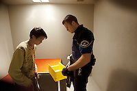 Switzerland. Geneva. A police officer is strip searching a prisoner in a cell at the Paquis police station. The inmate is a man from China, who was arrested because he caused a fight and is under the influence of alcohol. A strip search is a practice of searching a person for weapons or other contraband suspected of being hidden on their body or inside their clothing by requiring the person to remove some or all of his clothing. The strip search is a mandatory procedure which requires legal authority. It is done by a police officer once a person is arrested and locked in a cell. A police station or station house is a building which serves for police officers. The building contains temporary holding cells and interview/interrogation rooms. 18.03.12 © 2012 Didier Ruef *** Local Caption ***