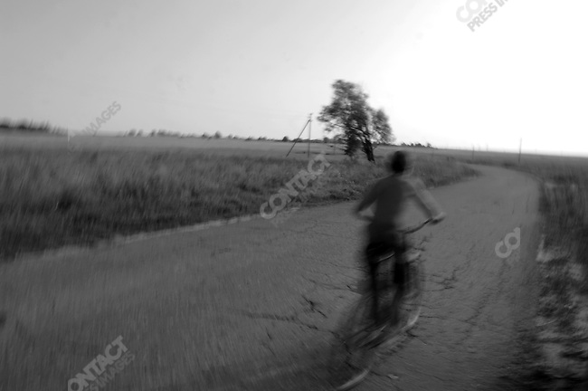 A boy cycled between the villages of Giblitsy and Pogost in Ryazan region. Russia, July 23, 2008.