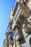 Balconies of houses historic street in city centre of Valletta, Malta