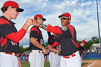 Batavia Muckdogs catcher Pablo Garcia (7) fist bumps teammate Ryley MacEachern (40) during introductions before a game against the State College Spikes on June 22, 2016 at Dwyer Stadium in Batavia, New York.  State College defeated Batavia 11-1.  (Mike Janes/Four Seam Images)