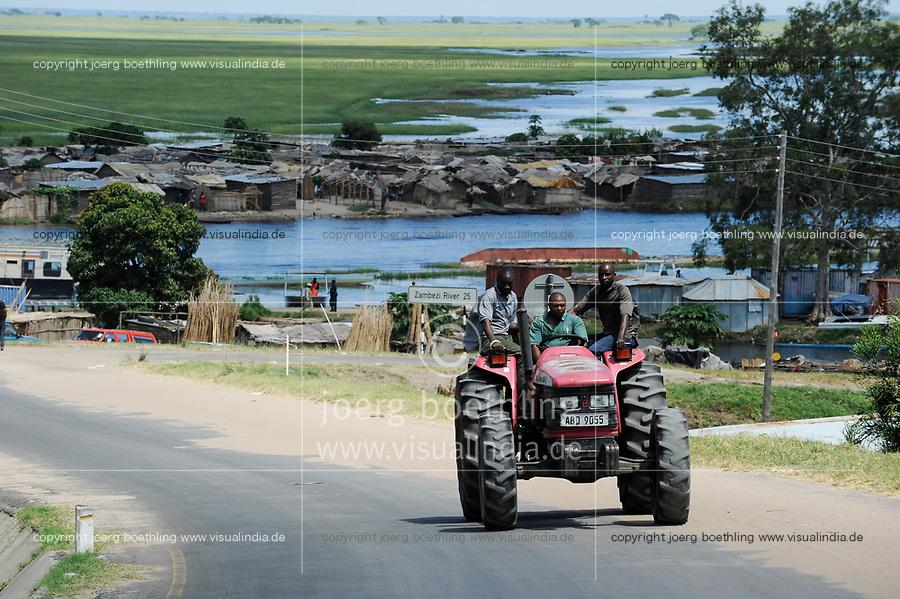 ZAMBIA Barotseland Mongu, Mulamba harbour at river Zambezi flood plain, Mahindra tractor, farmers doing paddy farming in the flood plains / SAMBIA Barotseland , Stadt Mongu , Hafen Mulamba in der Flutebene des Zambezi Fluss