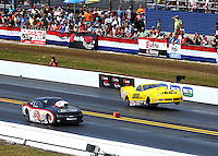 Mar 16, 2014; Gainesville, FL, USA; NHRA pro mod driver Troy Coughlin (right) does a wheelstand alongside Rickie Smith during the Gatornationals at Gainesville Raceway Mandatory Credit: Mark J. Rebilas-USA TODAY Sports