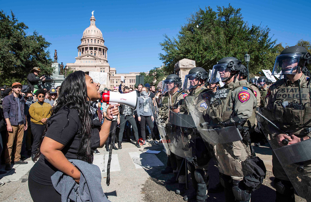 AUSTIN, TEXAS - A demonstrator with a bullhorn addresses the riot police at the Texas State Capitol during a White Lives Matter and Black Lives Matter demonstration.<br />