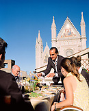 ITALY, Orvieto, Umbria, Chef Alex Palermo serving lunch on the rooftop of his family home with the Orvieto Cathedral in the background.