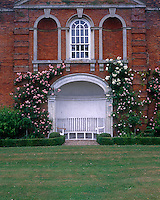 An elegant alcove in the distinctive red brick facade frames a curved bench overlooking the garden