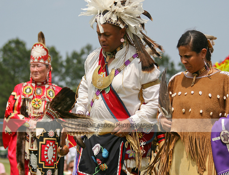 Native Americans in full traditional regalia parade in the dance circle at the 8th Annual Red Wing PowWow in Virginia Beach, Virginia.