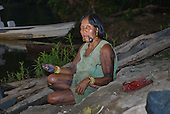 Pará State, Brazil. Aldeia Pukararankre (Kayapo). Woman smoking a chillom pipe, fishing.