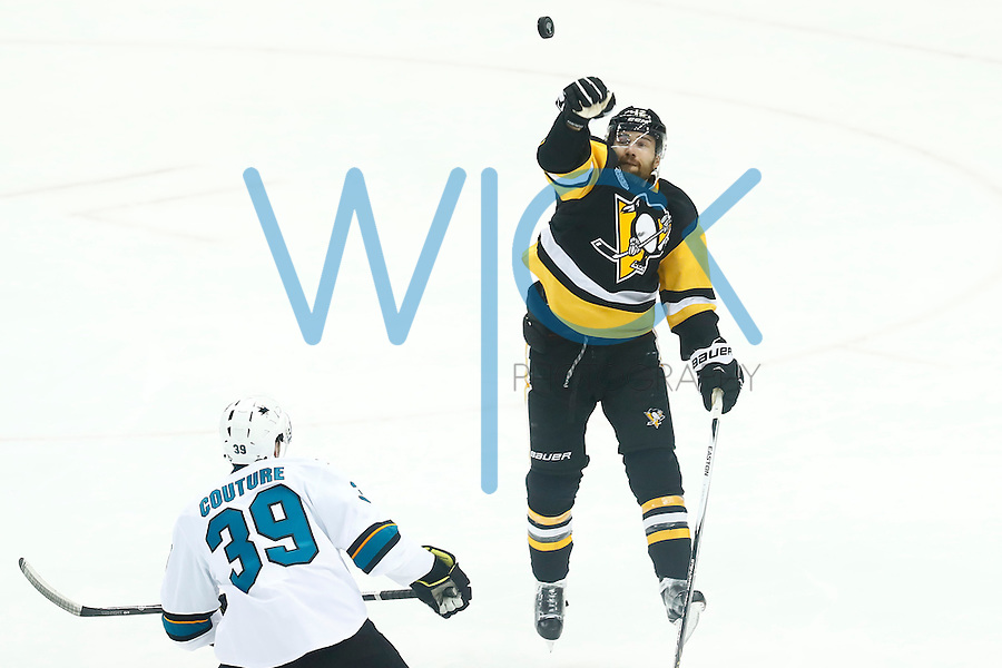 Ben Lovejoy #12 of the Pittsburgh Penguins knocks down the puck and out of the zone while shorthanded in front of Logan Couture #39 of the San Jose Sharks in the second period during game five of the Stanley Cup Final at Consol Energy Center in Pittsburgh, Pennsylvania on June 9, 2016. (Photo by Jared Wickerham / DKPS)