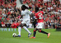 Pictured L-R: Bafetimbi Gomis of Swansea against Tyler Blackett of Manchester United. Saturday 16 August 2014<br />