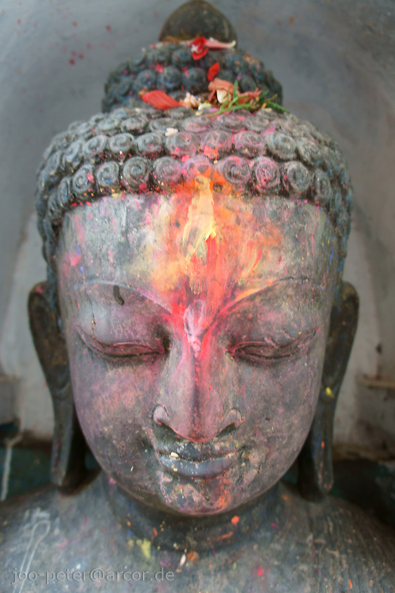 head of buddha (stone sculpture) next to stupa of buddhist temple Swayambhu in Kathmandu, Nepal, September 2011, full of colorful pigment, attached by worshippers. The red and yellow pigments look like a flame on the forehead of budda.