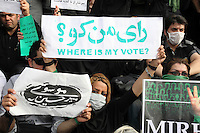 """""""Where is my vote?"""" A young woman in Toopkhaneh Square holds a placard. She is one of many protesters wearing masks as a symbol of their silent protest. Following a disputed election result, thousands of supporters of opposition candidate Mir-Hossein Mousavi took to the streets in protest..."""