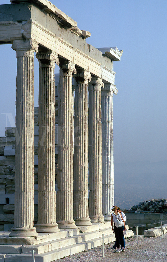 Tourists stand at the approach to a colonnade of the Erechtheion. Ionic columns and capitals.