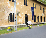Woman walking with umbrella for shade fort doorway historic town of Galle, Sri Lanka, Asia