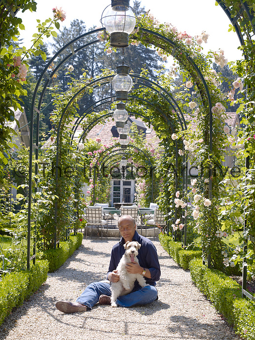 Fawaz Gruosi with his fox terrier in the rose allee