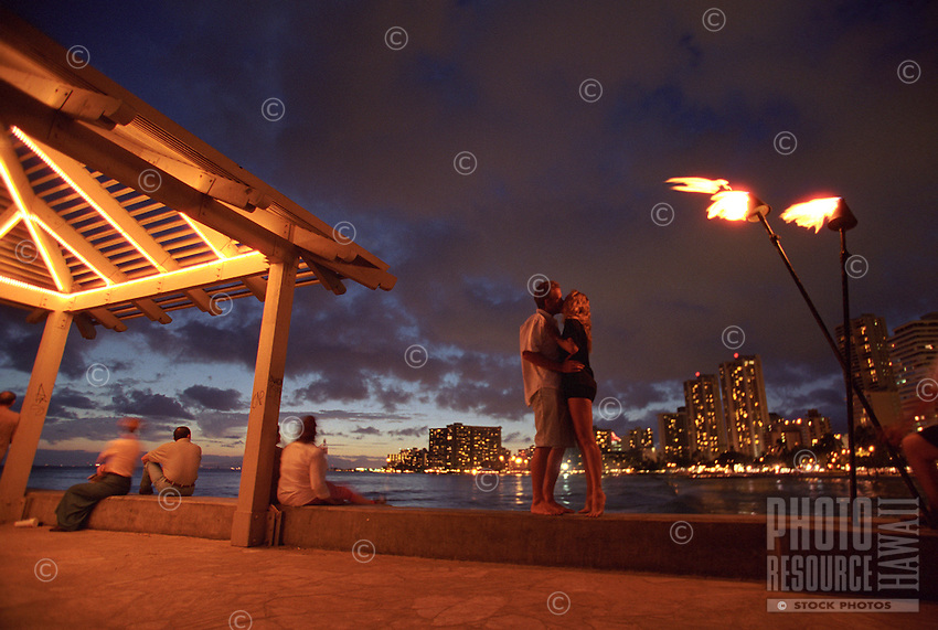 Couple kissing on a pier in Waikiki at sunset with tiki torches and hotel lights in background