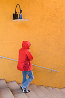 woman in red jacket against yellow wall in colorful La Placitas Village.