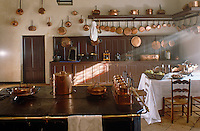 A old-fashioned range dominates this large kitchen which is decorated with a collection of copper pots and pans