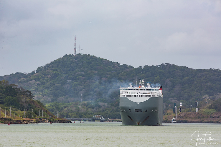 The Genius Highway, a large car carrier, moves through the Culebra Cut in the Panama Canal.  Panama.