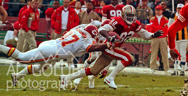San Francisco 49ers vs. Kansas City Chiefs at Candlestick Park Saturday, December 14, 1991.  49ers beat Chiefs 28-14.  Chiefs defensive tackle Dan Saleaumus (97) leaps to tackle 49er wide receiver John Taylor (82).