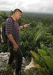 Ranger checks GPS on mountain overlooking Belize rainforest - Sarstoon-Temash National Park.