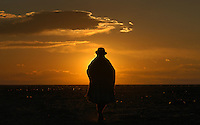 "Una mujer de la etnia aymara camina durante el atardecer a través del desierto que rodea la ciudad de Uyuni en la región sur de Bolivia.+ indio,   sol,  paisaje *An aymara indian woman walks at sunset  through the desert sourrounding  Uyuni city , in Southern Bolivia +landscape *Une femme de l'ethnie Aymara dans le désert aux abords de la ville, dans le sud de la Bolivie, au coucher du soleil. +indiens, indigènes, paysage For  the first time in its history,  in January 2014 the Dakar Rally will  be cross part of Bolivia, one of the wildest South American nations.  ""The organizers of the Dakar, attracted by the discovery of new spaces, were conquered by Bolivian landscapes that can be classified among the most striking of the continent,"" says the official site of the international race.<br />