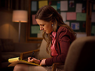 A counselor takes notes at a group meeting in her office