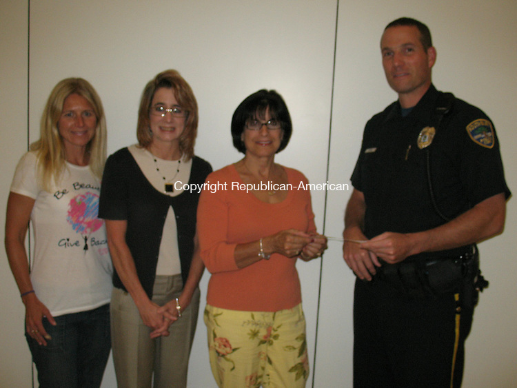 SOUTHBURY, CT. - 23 Sept. 2010 - 092310CG01 - Donald Nevins, a Southbury police officer, presents a $500 check on behalf of the Southbury Police Association to Dorrie Carolan, second from right, co-founder of the Newtown Parent Connection. Susanne Navas, left, and Noel Federle, co- leaders of Southbury & Middlebury Acting Responsibly Together (SMART), look on. The money will pay for an appearance Oct. 19 at Pomperaug High School by Norm Bossio, who will speak about putting family first, talking to teens and staying motivated as parents. The talk, which is free, is co-sponsored by SMART and the Newtown Parent Connection. Chris Gardner Republican-American