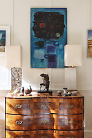 A marquetry cabinet occupies a wall of the living room which displays a collection of contemporary British art