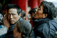 A tibetan pilgrim is praying in the middle of the crowd, trying to enter into the Main Assembly Hall where monks are chanting for the first day of the Great Prayer (Monlam Chenmo); in the monastery of Labrang. Xiahe, province of Gansu, China, March 09 2007.