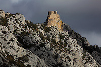 "Queribus Castle or Chateau de Queribus, Cathar Castle, Cucugnan, Corbieres, Aude, France. This view shows the steep rocky cliffs of its hilltop location. The castle, built from 13th to 16th centuries, is considered the last Cathar stronghold. It sits on a high peak at 728m. It is one of the ""Five Sons of Carcassonne"" or ""Cinq Fils de Carcassonne"". It is a listed monument historique and has been fully restored, restoration work being completed in 2002. Picture by Manuel Cohen"