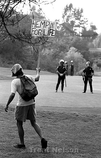Man with &quot;Hemp for Life&quot; sign taunts police during protests over President George Bush's visit to town.<br />