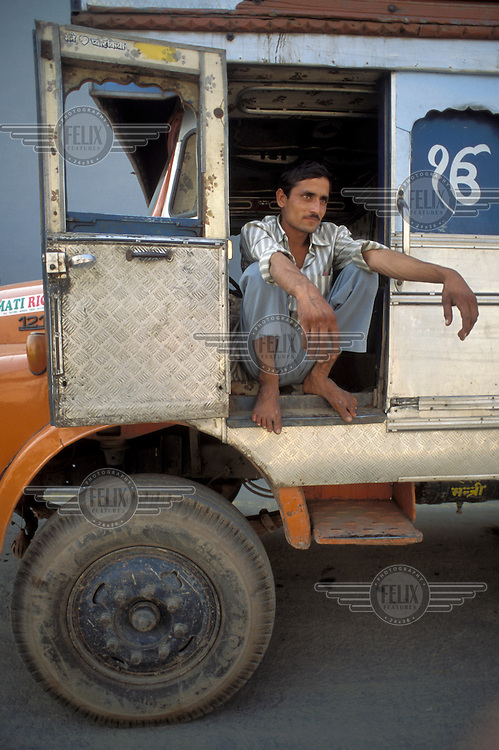 Lorry driver waits to load his truck at a basmati rice mill in Haryana.