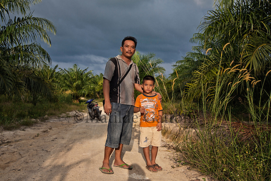 "Indonesia - Bangka Island - Rebo - Ajong Fang, 45, and his son Feri, 6 standing in their palm plantation. Ajong owns a mine and has worked on tin mining for ten years now. He extracts 200 kg of pure tin per day from his concession. He has also reclamated a 50-hectare previous mining concession, turning it into a palm oil plantation. ""I did it for my children"" he says, ""because tin mining will not be profitable in the long term""."