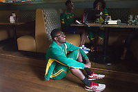 Hartford, CT - Friday June 13, 2014: Cameroonian-American David Abunaw sits on the floor after watching Cameroon miss a goal scoring attempt during the Cameroon vs. Mexico FIFA World Cup first round match at Damons Tavern in Hartford, CT.