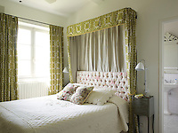 This elegant guest bedroom has curtains that match the bed canopy