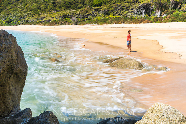 Young woman on pristine Anapai Bay on Abel Tasman Coast Track, Abel Tasman National Park, Nelson Region, South Island, New Zealand