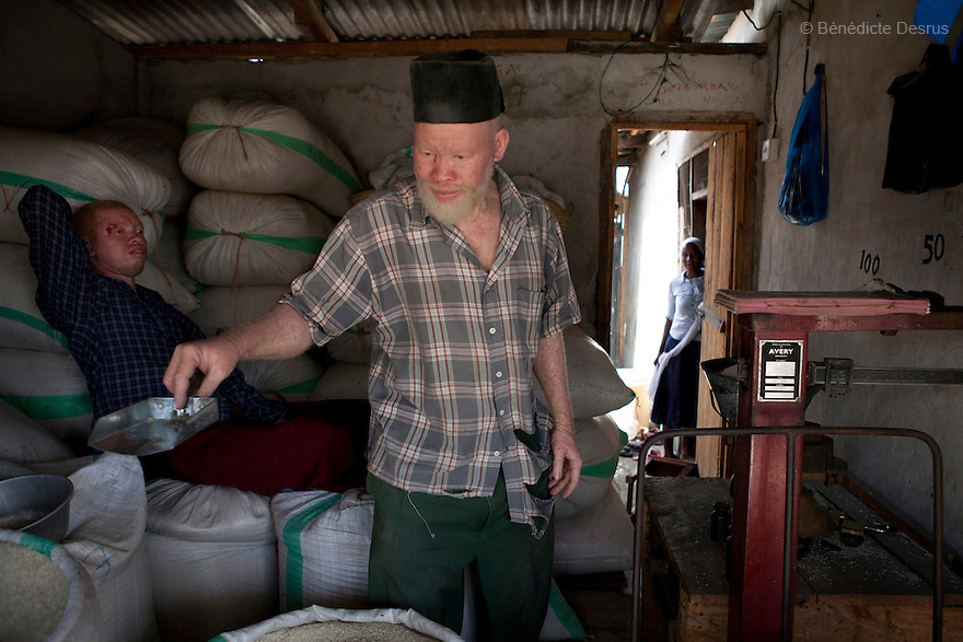 June 28, 2010 - Dar es Salaam, Tanzania - Ali Mohamed (R) and his son, Salehe Ally (L), working at the shop. Ali Mohamed is a 61 year old Muslim man with albinism living in Tanzania where he has a shop selling rice and grains. Ali married his first wife, Jutia Jalehe, in 1978. Jutia is also an albino and together they had 1 son with albinism named Salehe Ally. In 1983, Mohamed married his second wife, Nuru Mohamedy who did not have Albinism. Together they had 6 children, two of them with albinism and four of them without albinism. Albinism is a recessive gene but when two carriers of the gene have a child it has a one in four chance of getting albinism. Tanzania is believed to have Africa' s largest population of albinos, a genetic condition caused by a lack of melanin in the skin, eyes and hair and has an incidence seven times higher than elsewhere in the world. Over the last three years people with albinism have been threatened by an alarming increase in the criminal trade of Albino body parts. At least 53 albinos have been killed since 2007, some as young as six months old. Many more have been attacked with machetes and their limbs stolen while they are still alive. Witch doctors tell their clients that the body parts will bring them luck in love, life and business. The belief that albino body parts have magical powers has driven thousands of Africa's albinos into hiding, fearful of losing their lives and limbs to unscrupulous dealers who can make up to US$75,000 selling a complete dismembered set. The killings have now spread to neighboring countries, like Kenya, Uganda and Burundi and an international market for albino body parts has been rumored to reach as far as West Africa. Photo credit: Benedicte Desrus