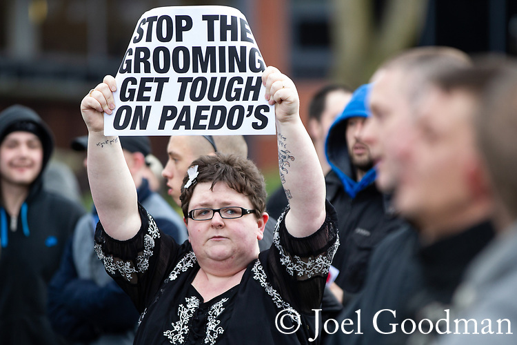 "© Joel Goodman - 07973 332324 . 03/03/2012 . Heywood , UK . A woman holds a sign that reads "" Stop the grooming get tough on paedo's [sic]"" .  The National Front hold a rally in protest against an alleged paedophile ring that had been operating in the area . There is currently (3rd March 2012) a case being tried at Liverpool Crown Court in relation to the allegations . Last Thursday (23rd February 2012) a protest organised in the town in relation to the same story resulted in Asian business being attacked by an angry mob . Photo credit : Joel Goodman"