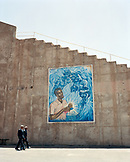 ERITREA, Asmara, business men walk by murals depicting the Eritrean-Ethopian War