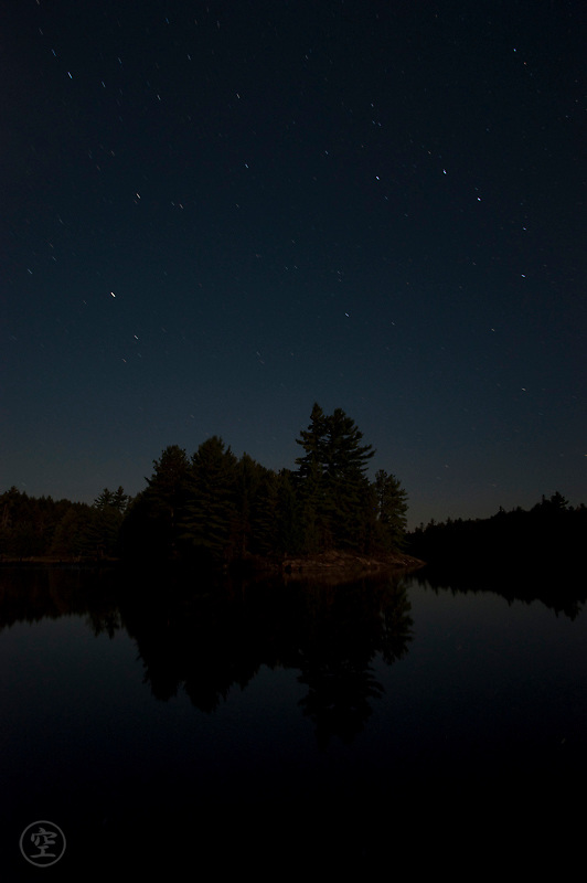 Stars reflect in the water and shine over the white pines and granite shores of Balsam lake, Killarney Provincial Park, Ontario, Canada