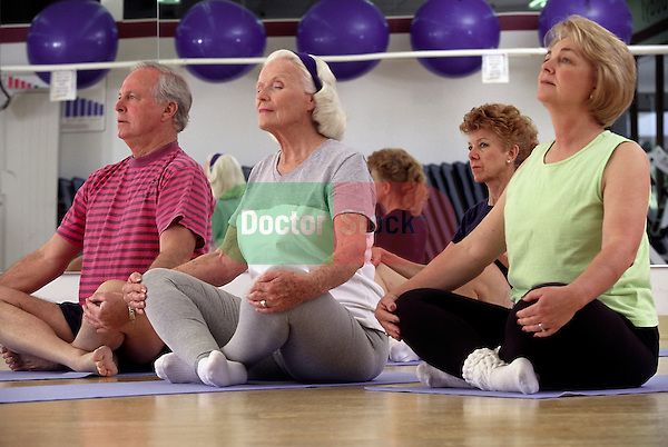 Senior man and women in Yoga class