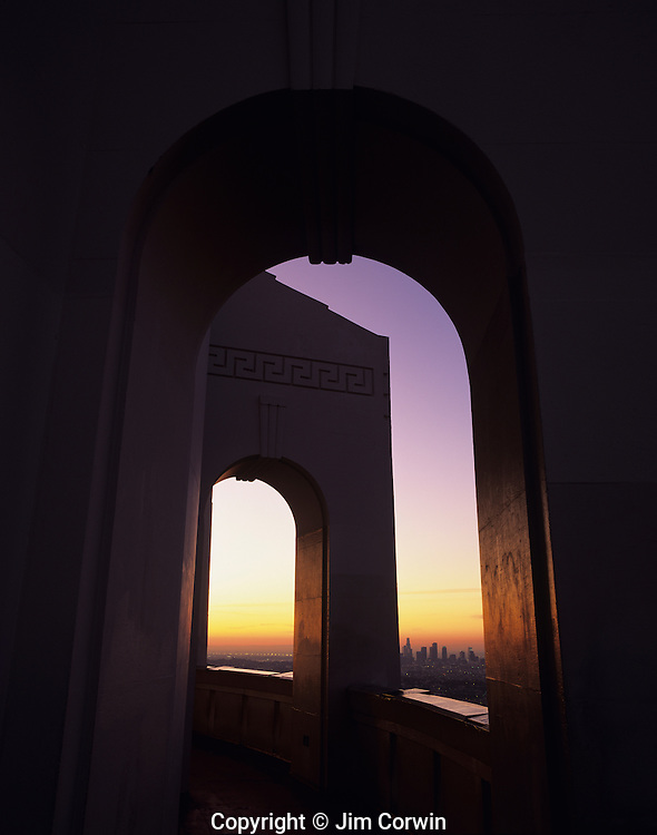 Sunrise over LA through archways at the Griffith Park Observatory, Downtown District with skyscrapers, Los Angeles, California USA