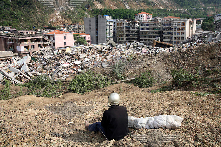 A man sits by the body of his son, a third grader, after personally recovering him from the ruins of a collapsed school complex in Beichuan. An earthquake measuring 7.9 on the richter scale hit Sichuan on 12/05/2008.