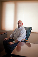 "Dr. Clinton ""Clint"" Merrill Jr. of Laramie, Wyoming poses for portraits inside of his empty oncology practice.  Merrill shuttered his practice in September of 2010.  His practice was unable to remain open largely because of Medicare's low payments on drugs used by the practice; according to the doctor, often times Medicare reimbursements were lower than the cost of the drug."