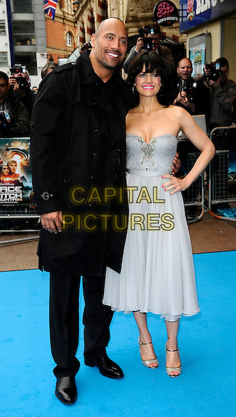 "DWAYNE ""THE ROCK"" JOHNSON & CARLA GUGINO.The UK film premiere of ""Race To Witch Mountain"" at Odeon Cinema West End, London, England..April 5th 2009.full length black jacket trousers sunglasses shades strapless blue silver pale grey gray dress hand on hip open toe ankle strap shoes cleavage.CAP/CAN.©Can Nguyen/Capital Pictures."