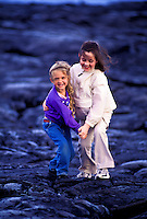 Two girls playing on a lava bed at Hawaii Volcanoes National park, Big Island