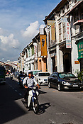 Motorists ride past restored heritage houses in the UNESCO heritage town - Georgetown of Penang, Malaysia. Photo: Sanjit Das/Panos